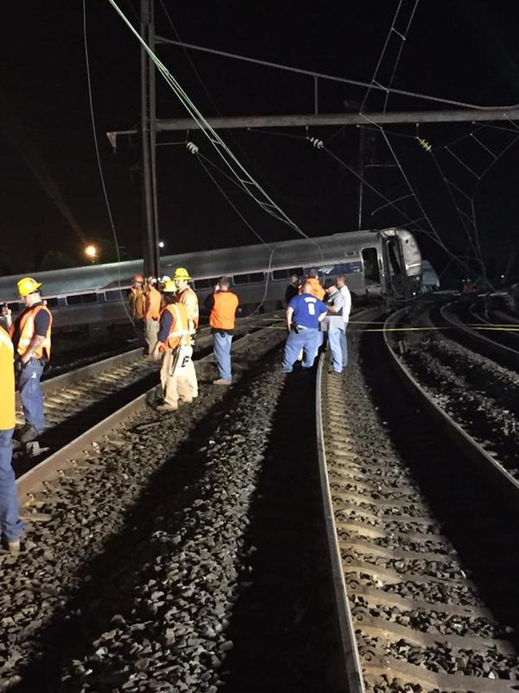 Emergency personnel and members of the Philadelphia Fire Department investigate the scene of a train accident in Philadelphia, Pennsylvania, in this handout photo provided by the Philadelphia Fire Department, May 13, 2015. Federal investigators have recovered the black box from the wreckage of an Amtrak train that derailed in Philadelphia and were reviewing data to determine what caused the crash that killed at least six people and injured more than 200, officials said on Wednesday. REUTERS/Philadelphia Fire Department/Handout FOR EDITORIAL USE ONLY. NOT FOR SALE FOR MARKETING OR ADVERTISING CAMPAIGNS. THIS IMAGE HAS BEEN SUPPLIED BY A THIRD PARTY. IT IS DISTRIBUTED, EXACTLY AS RECEIVED BY REUTERS, AS A SERVICE TO CLIENTS