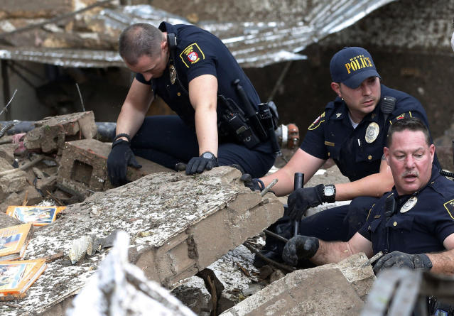 Moore police dig through the rubble of the Plaza Towers Elementary School following a tornado in Moore, Okla., Monday, May 20, 2013. A tornado as much as a mile (1.6 kilometers) wide with winds up to 200 mph (320 kph) roared through the Oklahoma City suburbs Monday, flattening entire neighborhoods, setting buildings on fire and landing a direct blow on an elementary school. (AP Photo/Sue Ogrocki)