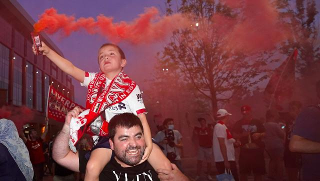A child holds a flare in hand as fans celebrate outside Liverpool's home ground The Anfield. AP