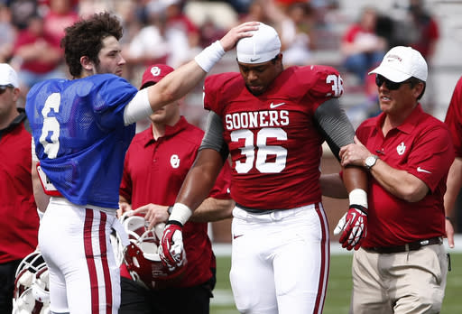 Oklahoma quarterback Baker Mayfield (6) checks on Dimitri Flowers (36) who was hurt in the fourth quarter of the annual NCAA college spring football game in Norman, Okla., Saturday, April 12, 2014. (AP Photo/Alonzo Adams)