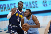 Memphis Grizzlies forward Justise Winslow, front, drives to the basket past Denver Nuggets forward Paul Millsap in the first half of an NBA basketball game Monday, April 19, 2021, in Denver. (AP Photo/David Zalubowski)