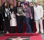"""Metal-rock star Ozzy Osbourne, center, poses with his family after he was honored with a star on the Hollywood Walk of Fame Friday, April 12, 2002, in the Hollywood section of Los Angeles. Osbourne currently stars in the MTV reality-show """"The Osbournes,"""" which chronicles the homelife of the singer, his wife, Sharon, second left, and two of his children, Kelly, 17, third from right, and Jack, 16, second right. At far left is Osbourne's older daughter Aimee and his son Louis, from a previous marriage, is at far right. (AP Photo/Nick Ut)"""