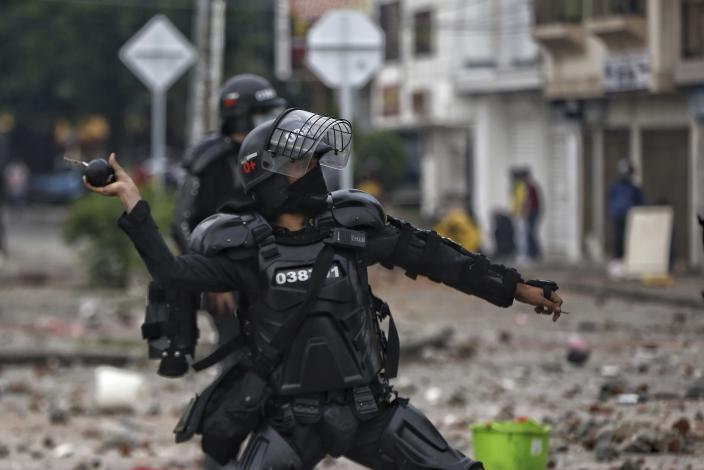 A police officer winds up to throw a stun grenade at protesters during a national strike against tax reform in Cali, Colombia, Monday, May 3, 2021. Colombia's President Ivan Duque withdrew the government-proposed tax reform on Sunday. (AP Photo/Andres Gonzalez)