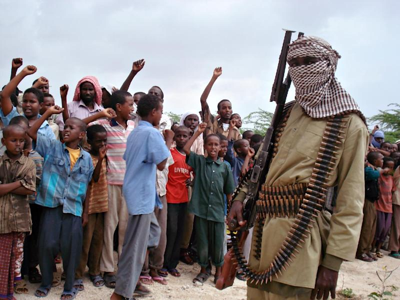 Somali boys chant as they watch hard-line Islamist fighters from the Al-Qaeda-linked Shebab parade in the streets of Mogadishu on October 30, 2009