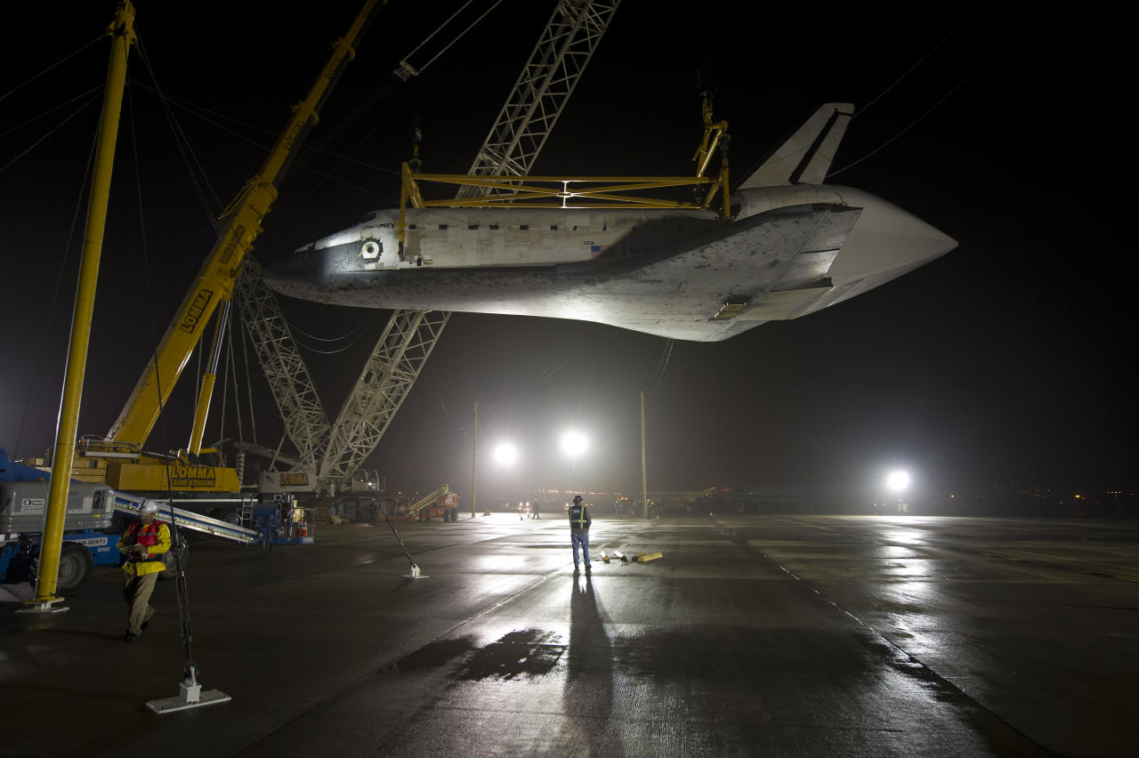 STERLING, VA - APRIL 19: In this handout provided by NASA, the space shuttle Discovery is suspended from a sling held by two cranes shortly after the NASA 747 Shuttle Carrier Aircraft (SCA) was pushed back from underneath at Washington Dulles International Airport on April 19, 2012, in Sterling, Virginia.  Discovery, the first orbiter retired from NASA's shuttle fleet, completed 39 missions, spent 365 days in space, orbited the Earth 5,830 times, and traveled 148,221,675 miles. NASA will transfer Discovery to the National Air and Space Museum to begin its new mission to commemorate past achievements in space and to educate and inspire future generations of explorers.  (Photo by NASA/Bill Ingalls via Getty Images)