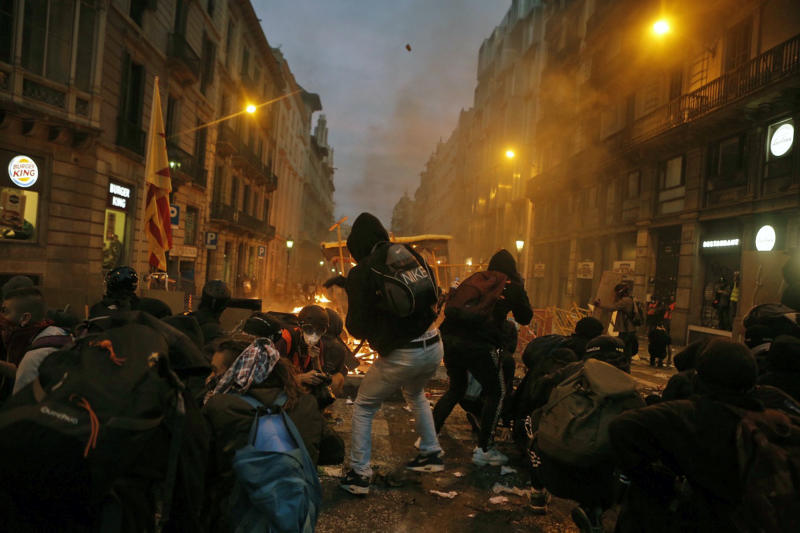 Protesters stand and crouch behind barricades on the fifth day of protests over the conviction of a dozen Catalan independence leaders in Barcelona, Spain, Friday, Oct. 18, 2019. Tens of thousands of flag-waving demonstrators demanding Catalonia???s independence and the release from prison of their separatist leaders have flooded downtown Barcelona. The protesters have poured into the city after some of them walked for three days in ???Freedom marches??? from towns across the northeastern Spanish region, joining students and workers who have also taken to the streets on a general strike day. (AP Photo/Joan Mateu)