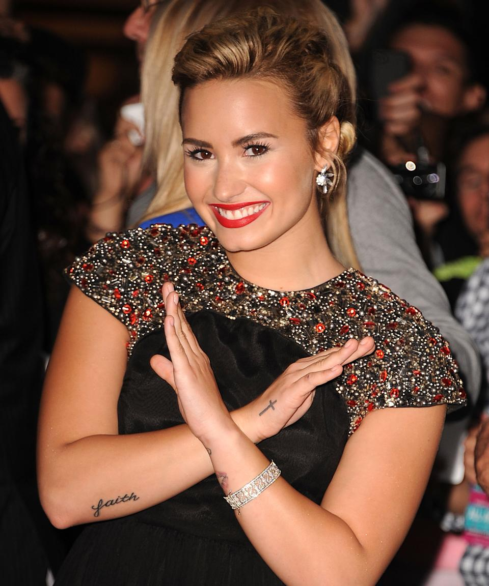 """<h3>Cross</h3><br><br>Lovato also added a black cross to the outside of her right hand as a tribute to her faith in 2011.<span class=""""copyright"""">Photo: Steve Granitz/WireImage.</span>"""