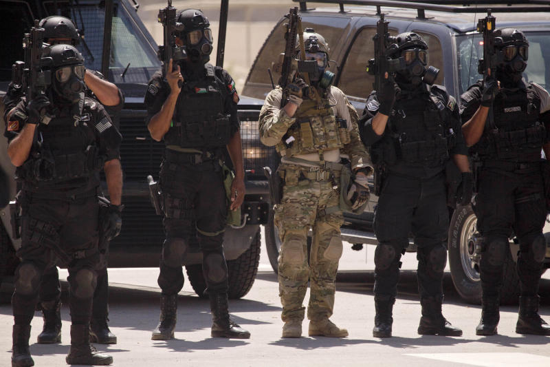 In this Thursday, June 20, 2013 photo, special operations forces from Iraq, Jordan and the U.S. stand in formation wearing gas masks following a combined demonstration as part of Eager Lion multinational military maneuvers at the King Abdullah Special Operations Training Center (KASOTC) in Amman, Jordan. The first Jordanian public official to speak publicly of the numbers of U.S. troops in the kingdom, Abdullah Ensour told reporters Saturday, June 22, 2013 that 200 of the personnel were experts training for how to handle a chemical attack. He said the remaining 700 are manning a Patriot missile defence system and F-16 fighter jets which Washington deployed this month in case the Syrian war worsens.(AP Photo/Maya Alleruzzo)