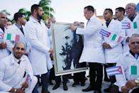 Cuban doctors hold an image of late Cuban President Fidel Castro during a farewell ceremony before departing to Italy to assist, amid concerns about the spread of the coronavirus disease (COVID-19) outbreak, in Havana