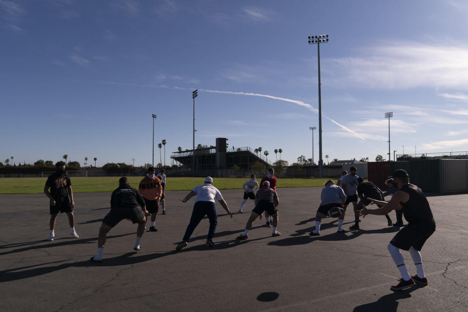 El Modena payers run a drill before the team's high school football game with El Dorado in Orange, Calif., Friday, March 19, 2021. High school football recently resumed playing football since the start of the pandemic as more California counties ease coronavirus restrictions and life in the nation's most populous state inches back to normalcy. (AP Photo/Jae C. Hong)