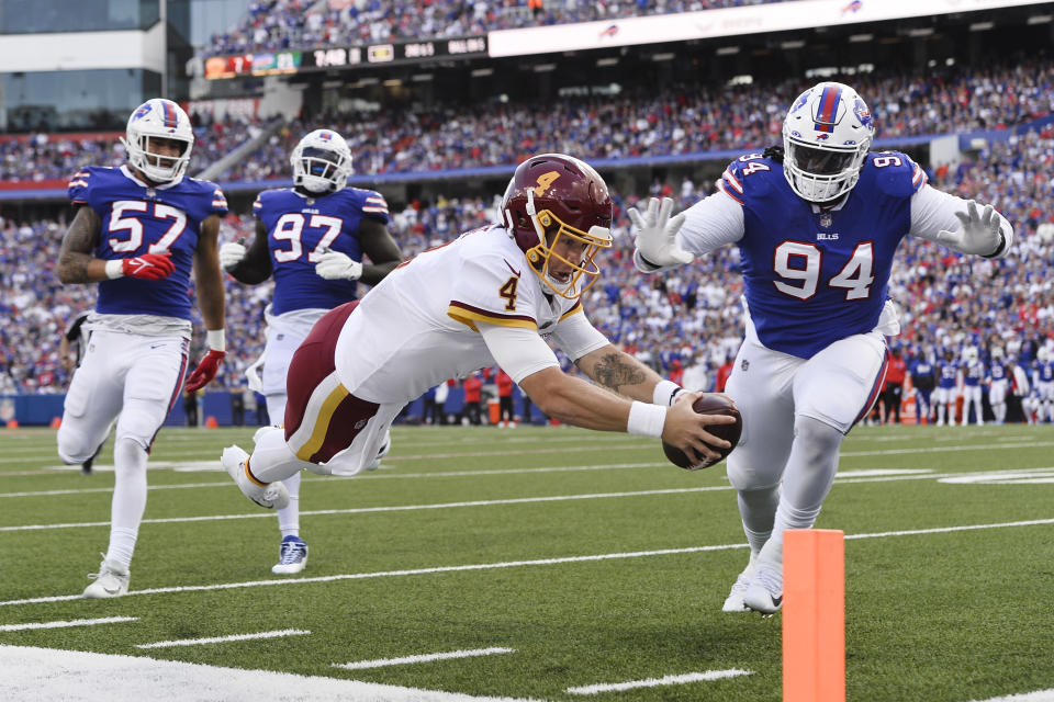 Washington Football Team quarterback Taylor Heinicke (4) dives past Buffalo Bills' Vernon Butler (94) for a touchdown as Bills' A.J. Epenesa (57) and Mario Addison (97) watch during the first half of an NFL football game Sunday, Sept. 26, 2021, in Orchard Park, N.Y. (AP Photo/Adrian Kraus)