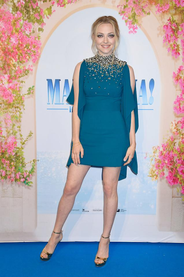 <p>Amanda Seyfriend brought 60s vibes in a caped Prada dress which featured a high neck and embellishment. <br /><em>[Photo: Rex]</em> </p>