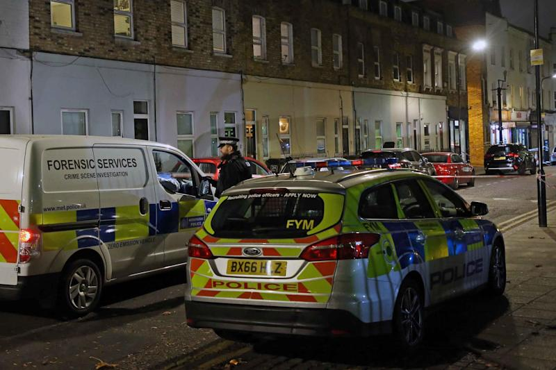 Police vehicles lined the street near the scene where the teenager was stabbed to death (NIGEL HOWARD)