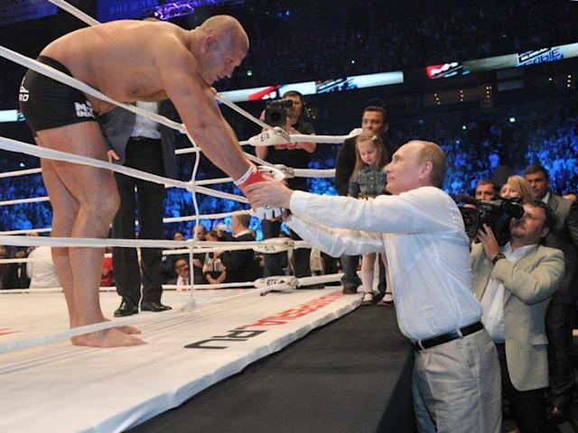 Fedor Emelianenko (L) shakes hands with Russian President Vladimir Putin following a 2012 match in Moscow. (The Associated Press)