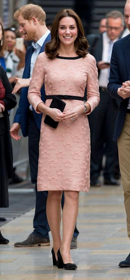 """<p>At Paddington Station, the Duchess wore a peachy-pink Orla Kiely dress with black accents around the waist and neckline, plus a black clutch and pumps to match. Despite her continuing <a rel=""""nofollow"""" href=""""http://www.townandcountrymag.com/society/tradition/a13026658/kate-middleton-paddington-bear/"""">battle with morning sickness</a>, she was was still able to dance with Paddington Bear and looked as fresh as her new haircut. </p>"""