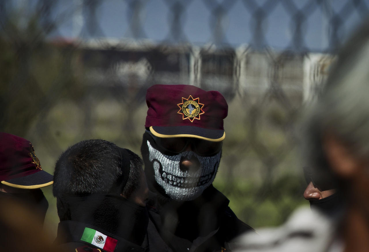 ALTERNATIVE CROP OF MXHM102 - A state police officer wearing a face mask stands behind the fence as relatives of inmates wait for news after a prison riot at Apodaca correctional state facility in Apodaca on the outskirts of Monterrey, Mexico, Sunday Feb. 19, 2012. A fight among inmates at the prison led to a riot that killed dozens on Sunday, according to a security official. (AP Photo/Hand Maximo Musielik)