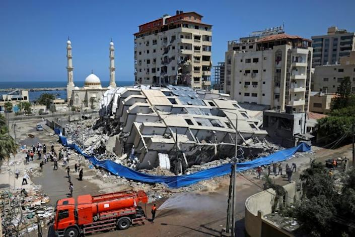 Palestinian volunteers and municipal workers clear the rubble of buildings, recently destroyed by Israeli strikes, in Gaza City's Rimal district