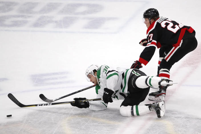 Dallas Stars center Joel L'Esperance (38) and Chicago Blackhawks defenseman Adam Boqvist (27) compete for the puck during the first period of an NHL hockey game Thursday, April 8, 2021, in Chicago. (AP Photo/Jeff Haynes)