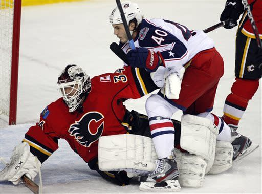 Columbus Blue Jackets' Jared Boll, right, knocks Calgary Flames goalie Miikka Kiprusoff, from Finland, to the ice during the second period of an NHL hockey game Friday, March 29, 2013, in Calgary, Alberta. (AP Photo/The Canadian Press, Jeff McIntosh)