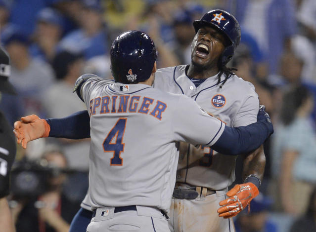<p>Houston Astros center fielder George Springer (4) celebrates with teammate Cameron Maybin (3) after hitting a two-run home run against the Los Angeles Dodgers in the 11th inning in game two of the 2017 World Series at Dodger Stadium. Mandatory Credit: Gary A. Vasquez-USA TODAY Sports </p>