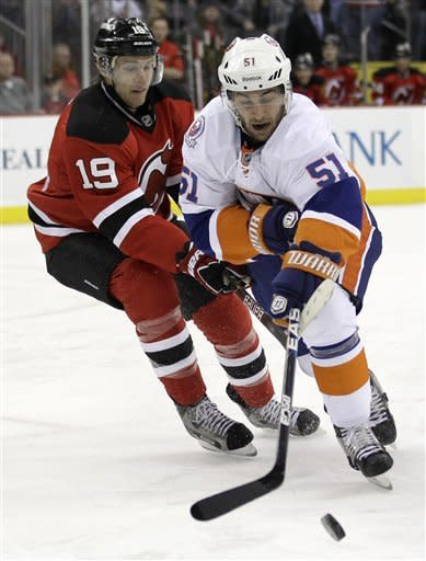 New York Islanders' Frans Nielsen (51), of Denmark, and New Jersey Devils' Travis Zajac (19) compete for the puck in the first period of an NHL hockey game Tuesday, April 3, 2012, in Newark, N.J. (AP Photo/Julio Cortez)