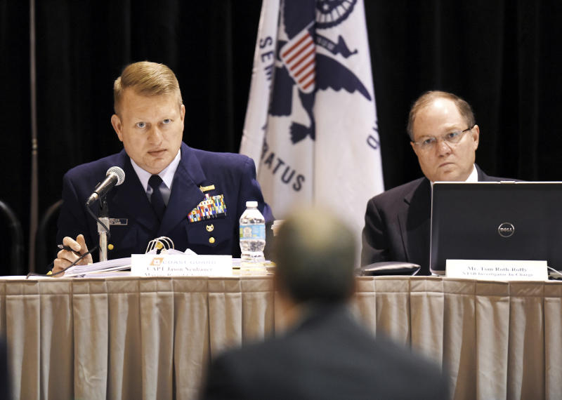 FILE - In this Feb. 18, 2016 file photo, Coast Guard Captain Jason Neubauer, left, the chairman of the El Faro hearing board and Tom Roth-Roffy, the NTSB Investigator-In-Charge listen as Charles Baird, the former second mate of the El Faro answers questions from Neubauer during a hearing investigating the ship's sinking, in Jacksonville, Fla. In a report released Sunday, Oct. 1, 2017, the Coast Guard says the primary cause of the sinking of a cargo ship two years ago that killed all 33 aboard was Capt. Michael Davidson misreading both the strength of a hurricane and his overestimation of the ship's strength. (Bob Self /The Florida Times-Union via AP, File)