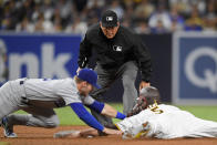 San Diego Padres right fielder Wil Myers (5) steals second base ahead of the tag of Los Angeles Dodgers second baseman Gavin Lux (9) as umpire Mark Carlson makes the call during the sixth inning of a baseball game Tuesday, June 22, 2021, in San Diego. (AP Photo/Denis Poroy)