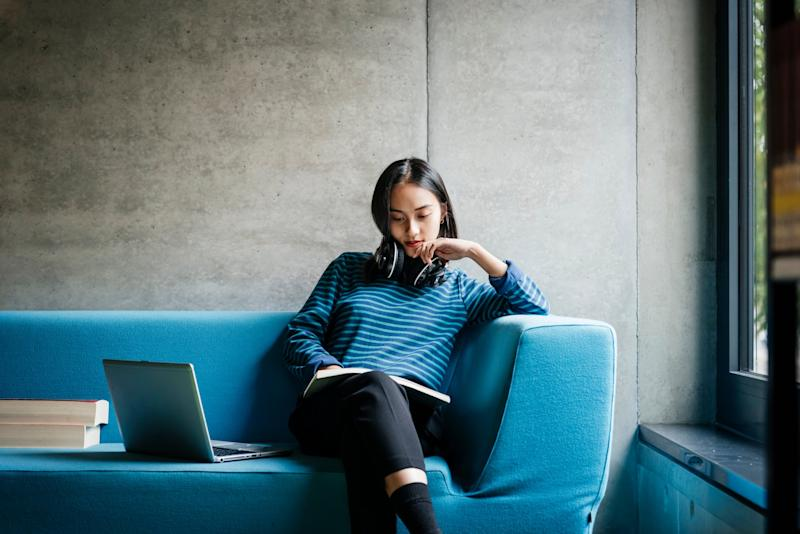 A young woman sitting on a couch looking at a laptop in a quiet library space.