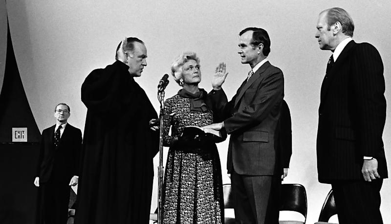 President Gerald R. Ford and Barbara Bush watch as Justice Potter Stewart swears in George H.W. Bush as the new Director of the CIA, at CIA HQ in Langley, Virginia on Jan. 26, 1976. The outgoing Director William Colby is at the left in the background.