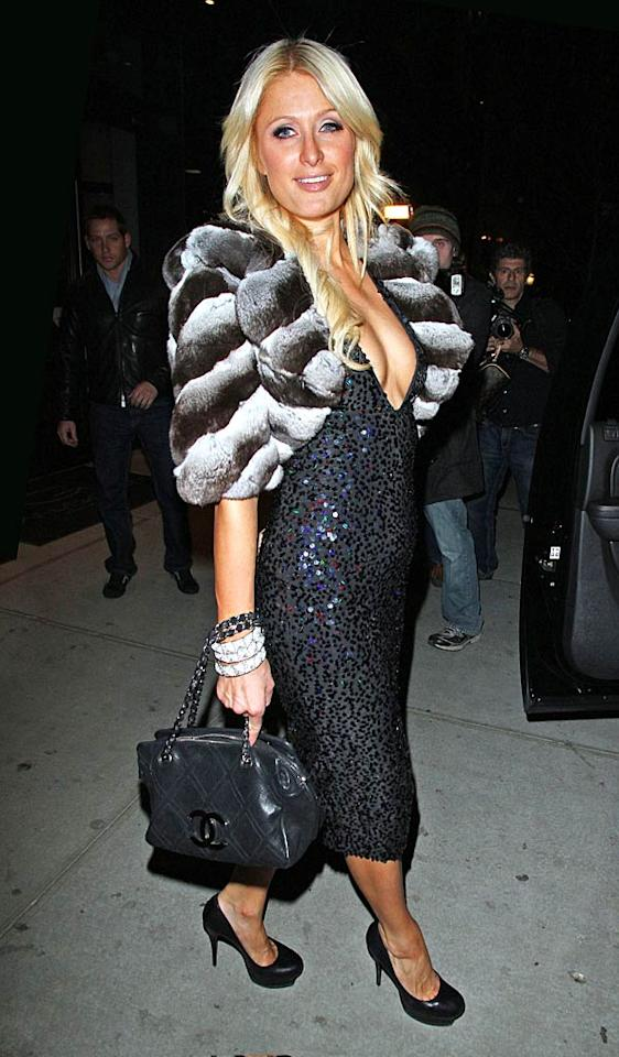 "Later that night, Paris was spotted heading to NYC's LAVO (Italian restaurant/nightclub) in a fur shrug, platform pumps, and a gray dress, which featured a plunging neckline and thousands of sequins. Jackson Lee/<a href=""http://www.splashnewsonline.com"" target=""new"">Splash News</a> - February 17, 2011"
