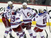 New York Rangers defenseman Dan Girardi, second from right, celebrates with teammates Artem Anisimov, left, Brad Richards, and Marc Staal, right, after scoring against the New Jersey devils during the third period of Game 3 of an NHL hockey Stanley Cup Eastern Conference final playoff series, Saturday, May 19, 2012, in Newark, N.J. (AP Photo/Julio Cortez)