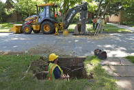 A Denver Water crew works to replace a lead water service line installed in 1927 with a new copper one at a private home on Thursday, June 17, 2021, in Denver. While President Joe Biden's infrastructure bill proposes $45 million for eliminating lead pipes and service lines, some utility companies and municipalities have already started replacing them. (AP Photo/Brittany Peterson)