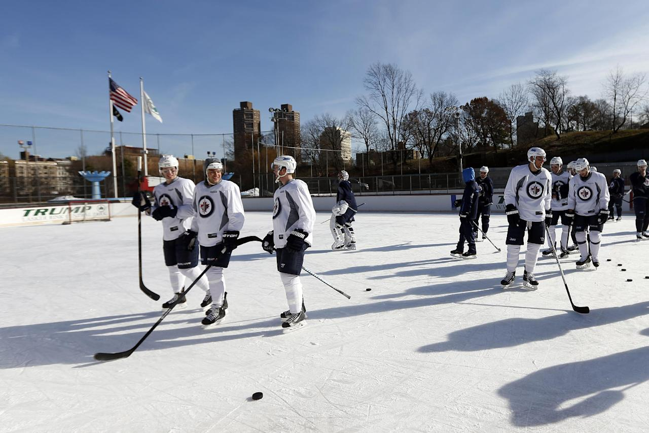 The Winnipeg Jets skate on the ice during NHL hockey practice at Lasker Rink in New York's Central Park, Saturday, Nov. 30, 2013. (AP Photo/Jason DeCrow)