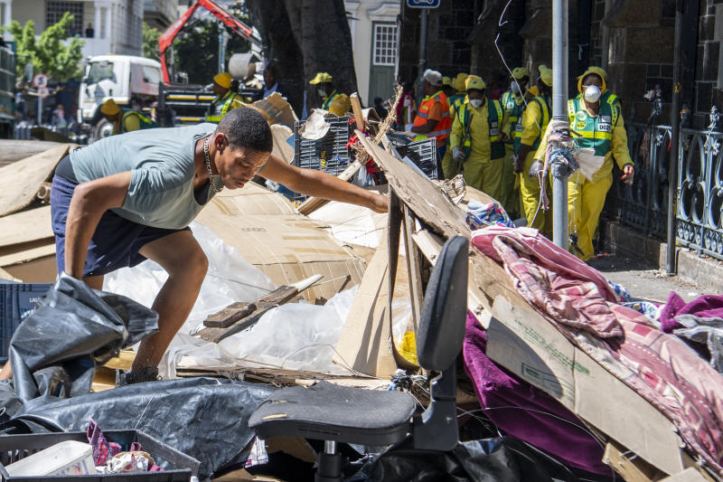 A man gathers his belongings, outside the Central Methodist Mission Church in Cape Town, South Africa, Sunday, March 1, 2020 as city officials and police move in to evict people. Hundreds of migrants have been removed from central Cape Town by South African authorities following a months-long stand-off. The migrants removed on Sunday had demanded to be relocated to other countries claiming they had been threatened by xenophobic violence last year.  (AP Photo)