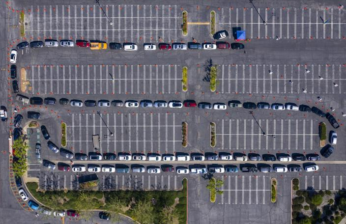 Aerial view shows a serpentine trail of cars winding around an empty parking lot.