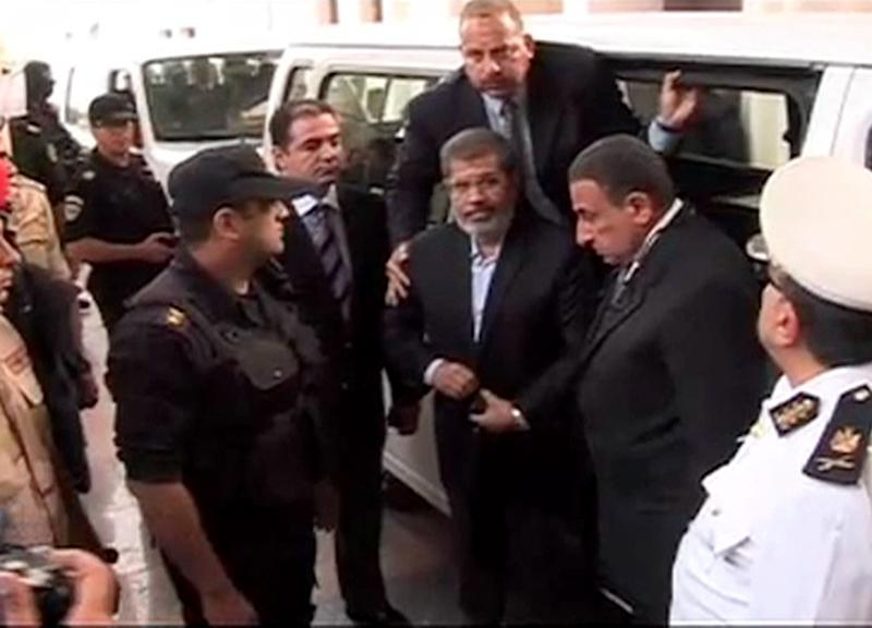 "This image made from video provided by Egypt's Interior Ministry shows ousted President Mohammed Morsi,center, arrives for a trial hearing in Cairo, Egypt, Monday, Nov. 3, 2013. Emerging from four months in secret detention, Egypt's deposed Islamist president defiantly rejected a court's authority to try him Monday, saying he was the country's ""legitimate"" leader and those that overthrew him should face charges instead.(AP Photo/Egyptian Interior Ministry)"