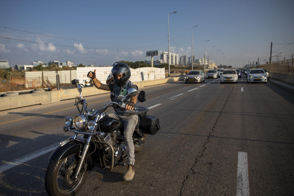 """A convoy of cars slow down the traffic as they staged demonstration against the Health Ministry's """"green pass"""" restrictions, on Ayalon highway, in Tel Aviv, Israel, Sunday, Oct. 3, 2021. Israel restricted its coronavirus """"green pass"""" on Sunday to allow only those who have received a COVID-19 booster or recently recovered to enter indoor events, sparking protests by opponents who say the system is a form of forced vaccination. (AP Photo/Oded Balilty)"""