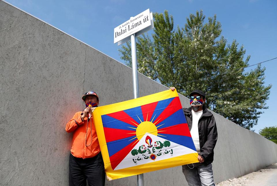 Activists hold a Tibetan flag next to a sign in a street renamed 'Dalai Lama', near the planned site of a Chinese university. Source: Reuters