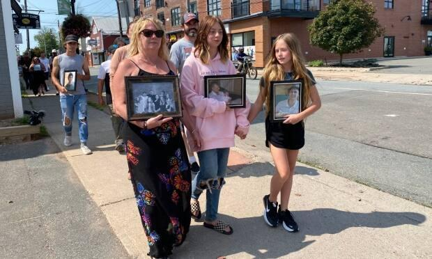 Tony Walsh's mother, Susan Robben, and his daughter, Maddie Chiasson, lead a walk through Truro, N.S., to mark the second anniversary of his disappearance.  (Carolyn Ray/CBC - image credit)
