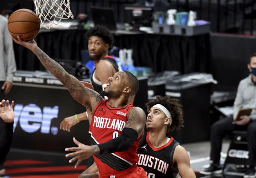 Portland Trail Blazers guard Damian Lillard drives to the basket past Houston Rockets guard Brodric Thomas during the second half of an NBA basketball game in Portland, Ore., Saturday, Dec. 26, 2020. The Blazers won 128-126 in overtime. (AP Photo/Steve Dykes)