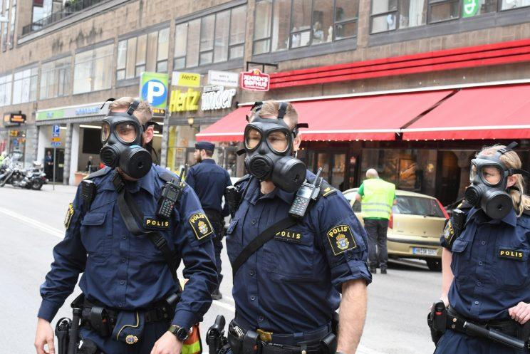 Officers in gas masks attend the scene (Rex Features)