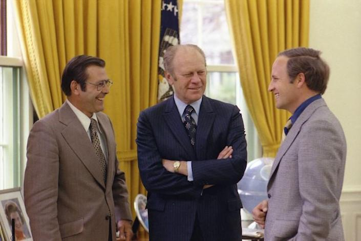 File photo of former US President Ford talking with his Chief of Staff Rumsfeld and Rumsfeld's assistant Cheney in the Oval Office