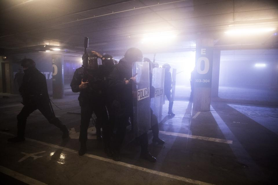 In this Monday, Oct. 14, 2019 photo, Spanish police in action during clashes with pro-independence protesters during a demonstration at El Prat airport, outskirts of Barcelona, Spain. Riot police engaged in a running battle with angry protesters outside Barcelona's airport Monday after Spain's Supreme Court convicted 12 separatist leaders of illegally promoting the wealthy Catalonia region's independence and sentenced nine of them to prison. (AP Photo/Joan Mateu)
