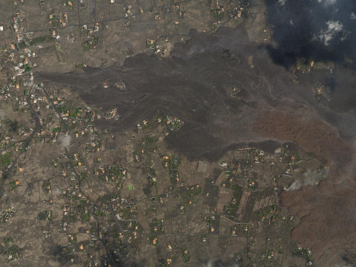 In this Saturday, Sept. 25, 2021 satellite photo from Planet Labs Inc. lava and ash from a volcano on the Canary island of La Palma, Spain can be seen. A Spanish island volcano that has buried more than 500 buildings and displaced over 6,000 people since last week lessened its activity on Monday, although scientists warned that it was too early to declare the eruption phase finished and authorities ordered residents to stay indoors to avoid the unhealthy fumes from lava meeting sea waters. (Planet Labs Inc. via AP)