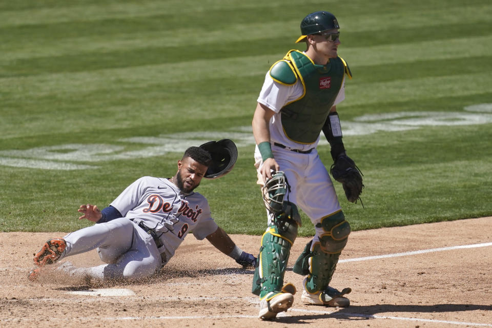 Detroit Tigers' Willi Castro, left, slides home to score behind Oakland Athletics catcher Sean Murphy during the sixth inning of a baseball game in Oakland, Calif., Sunday, April 18, 2021. (AP Photo/Jeff Chiu)