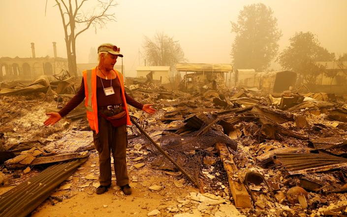 A man wearing an wearing an orange vest stands below a hazy sky amid an expanse of fire-destroyed rubble.