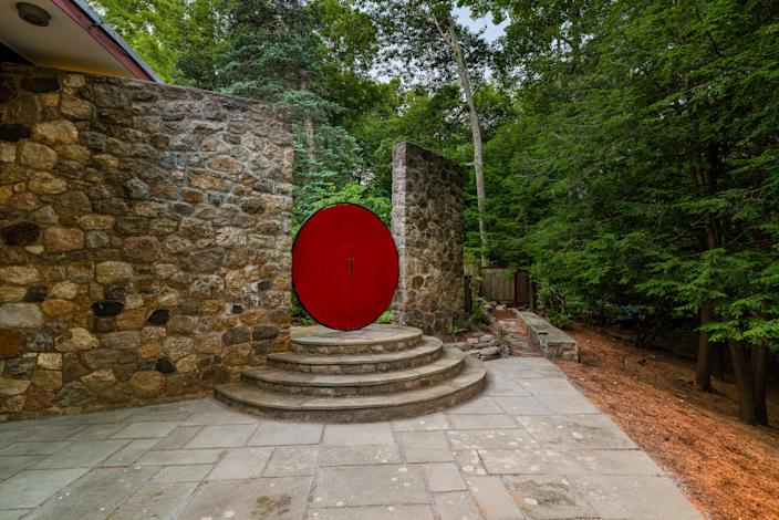 "<div class=""caption""> Throughout the 7.5-acre property are outdoor elements that add pops of red, like this moon gate. </div> <cite class=""credit"">Photo: Kyle P Norton / Courtesy of Douglas Elliman</cite>"