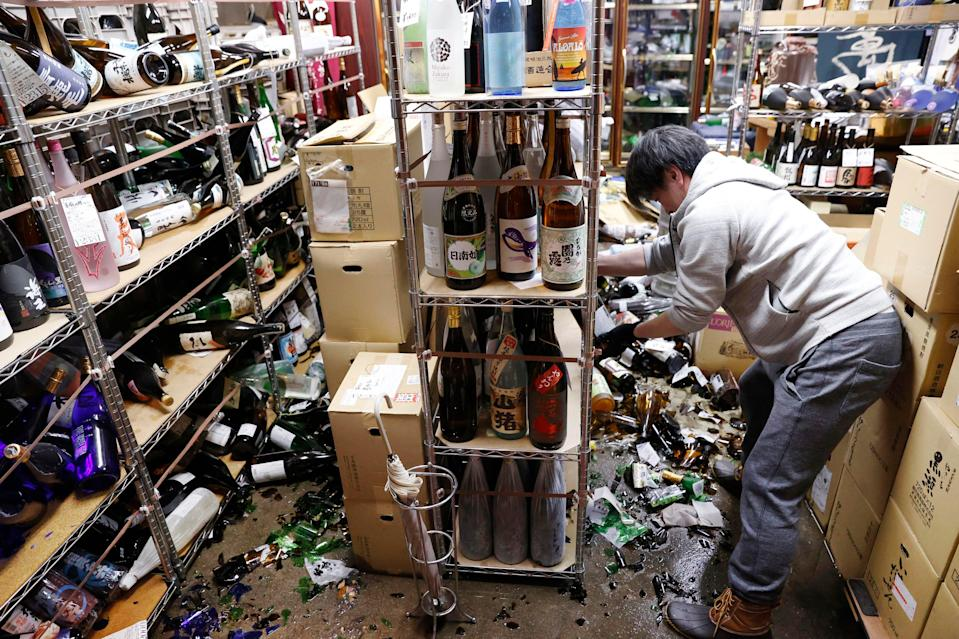 A liquor shop's manager clears the damaged bottles following an earthquake in Fukushima, northeastern JapanAP