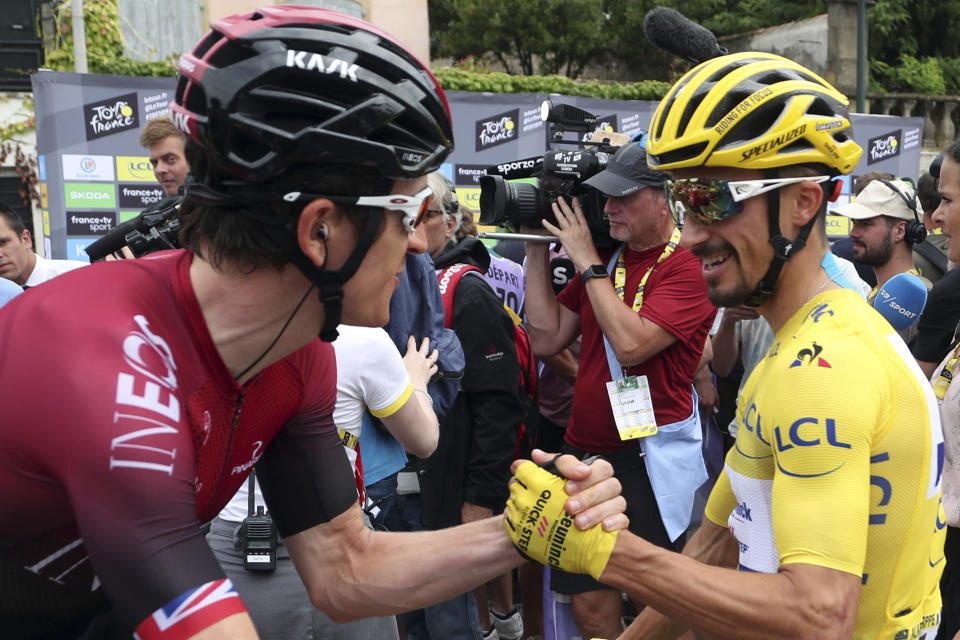 France's Julian Alaphilippe wearing the overall leader's yellow jersey shakes hands with Britain's Geraint Thomas as they arrive at the start of the fifteenth stage of the Tour de France cycling race over 185 kilometers (114,95 miles) with start in Limoux and finish in Prat d'Albis, France, Sunday, July 21, 2019. (AP Photo/Thibault Camus)