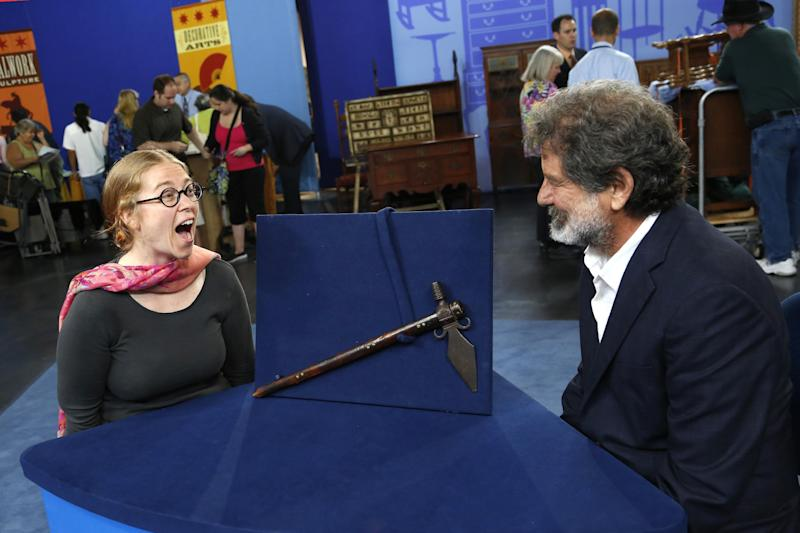 """This June 22, 2013 photo released by PBS shows Ted Trotta, of Trotta-Bono, Ltd., right, looking at Lisa as she reacts about information about her Spontoon Tomahawk Pipe during the taping of the popular appraisal show """"Antiques Roadshow,"""" in Anaheim, Calif. Top-rated PBS series """"Antiques Roadshow"""" is on the move, taping programs in eight U.S. cities for its upcoming 18th season.(AP Photo/PBS)"""